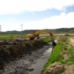 An excavator cleans a canal on the Running Y Ranch.