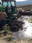 A John Deere tractor with rototiller stuck in a spring on the Running Y Ranch.