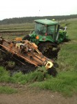 A John Deere 8430T with rototiller stuck in a ditch in pasture on the Running Y Ranch.