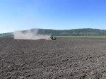 A tractor works a field to break up the ground to make it suitable for chipping potatoes at the Running Y Ranch.