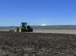 a four wheel drive John Deere tractor discs a field on Lower Klamath with Mt. Shasta in the background.